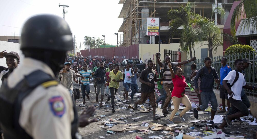A police officer looks on as a crowd enters the Delimart supermarket complex, which had been burned during two days of protests against a planned hike in fuel prices in Port-au-Prince, Haiti, Sunday, July 8, 2018.