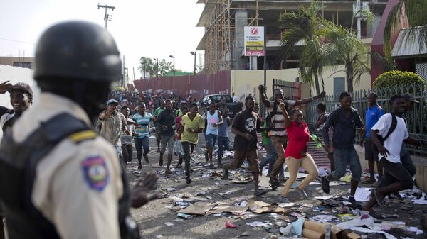 A police officer looks on as a crowd enters the Delimart supermarket complex, which had been burned during two days of protests against a planned hike in fuel prices in Port-au-Prince, Haiti, Sunday, July 8, 2018. - Sputnik Italia