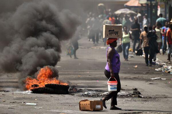 Una donna passa vicino alla gomma che sta bruciando a Port-au-Prince, Haiti. - Sputnik Italia