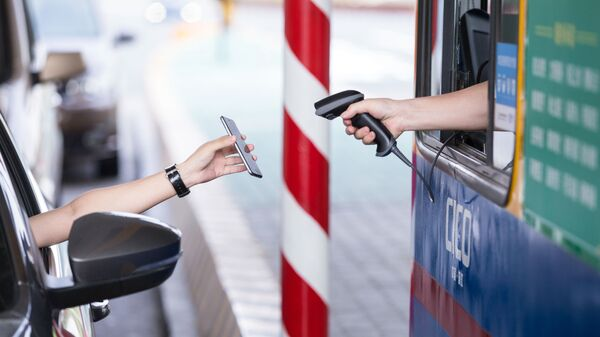 This picture taken on August 26, 2016 shows a driver uses his smartphone to pay the highway toll by way of Alipay, an app of Alibaba's online payment service, at Pengbu toll station on the Hangzhou-Ningbo Expressway in Hangzhou in Zhejiang province on September 21, 2016 - Sputnik Italia