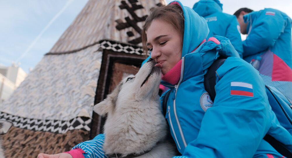 Un'atleta russa accolta dalla mascotte dei giochi, la cagnetta Laika