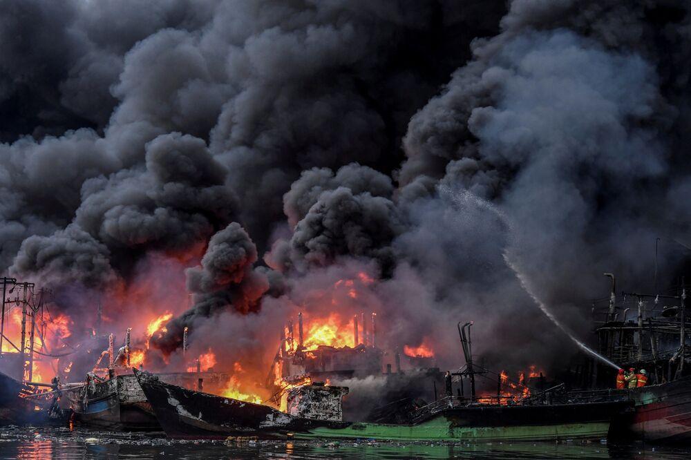 I vigili del fuoco estinguono il rogo nel porto di Muara Baru a Giacarta, Indonesia.