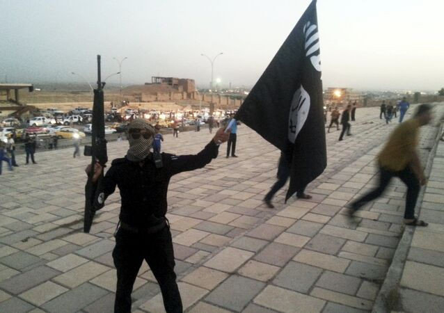A fighter of the Islamic State of Iraq and the Levant (ISIL) holds an ISIL flag and a weapon on a street in the city of Mosul, Iraq, in this June 23, 2014 file photo
