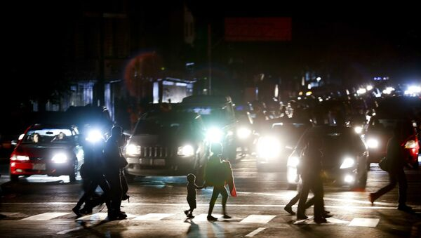 Residents cross a street in the dark after a power outage in Caracas, Venezuela, Thursday, March 7, 2019. A power outage left much of Venezuela in the dark early Thursday evening in what appeared to be one of the largest blackouts yet in a country where power failures have become increasingly common. Crowds of commuters in capital city Caracas were walking home after metro service ground to a halt and traffic snarled as cars struggled to navigate intersections where stoplights were out. - Sputnik Italia