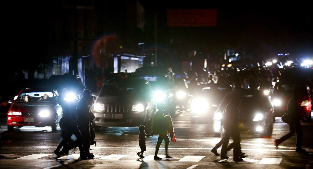 Residents cross a street in the dark after a power outage in Caracas, Venezuela, Thursday, March 7, 2019. A power outage left much of Venezuela in the dark early Thursday evening in what appeared to be one of the largest blackouts yet in a country where power failures have become increasingly common. Crowds of commuters in capital city Caracas were walking home after metro service ground to a halt and traffic snarled as cars struggled to navigate intersections where stoplights were out.