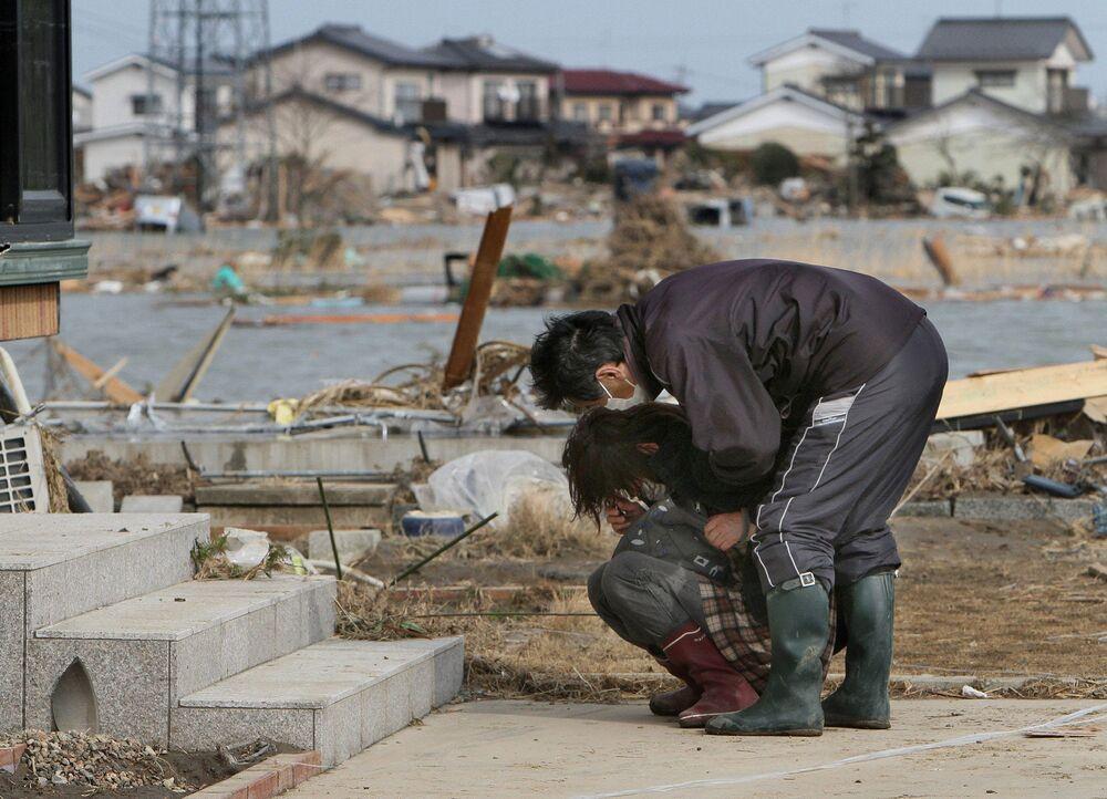 Un uomo cerca di confortare una donna in lacrime a Watari nella prefettura di Miyagi, 3 giorni dopo terremoto e tsunami
