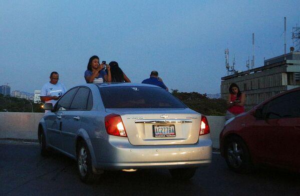 ساکنان کاراکاس در بزرگراه در حال تلاش برای دریافت سیگنال از تلفن همراه هستند - Sputnik International