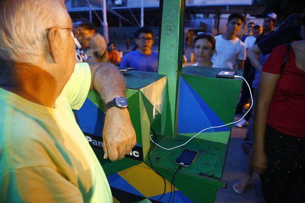 شارژ موبایل در نیروگاه های خورشیدی در میدان کاراکاس - Sputnik ایتالیا