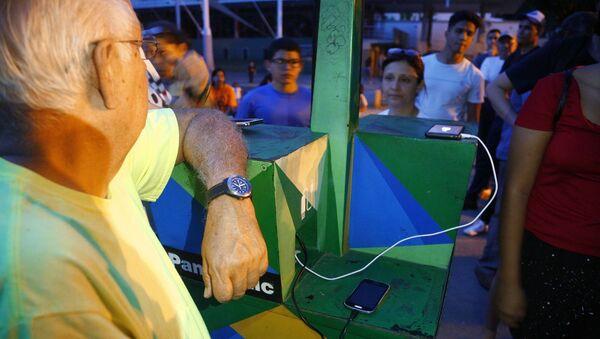 Ricarica cellulare alle colonnine elettriche solari in piazza a Caracas - Sputnik Italia