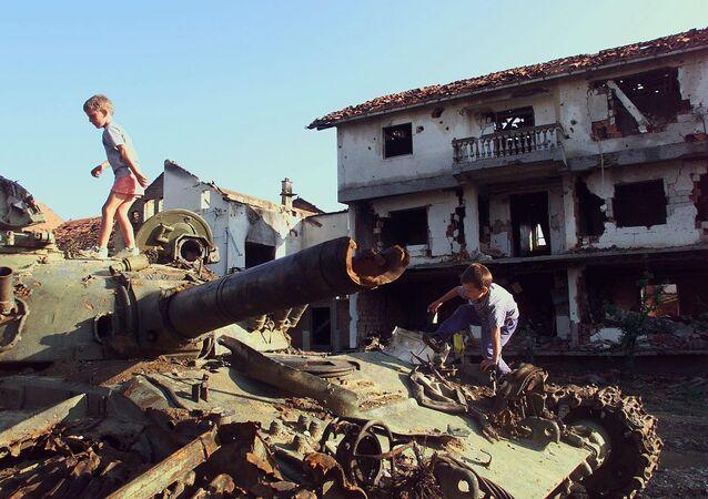Bambini stanno giocando su un carro armato serbo distrutto nel bombardamento della NATO nella città jugoslava di Klina, 1999.