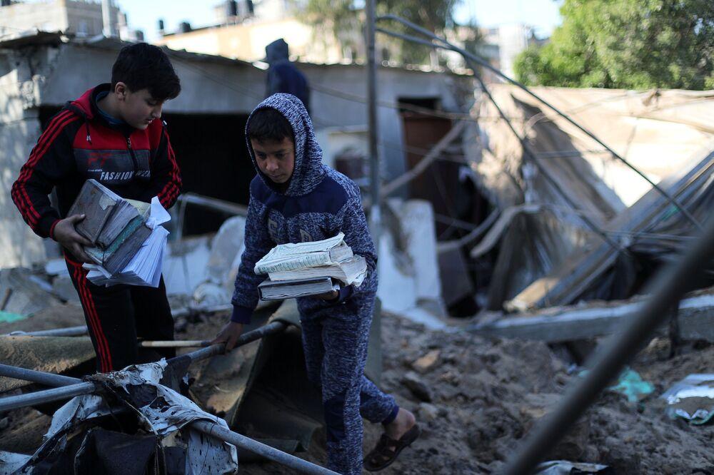 Bambini palestinesi raccolgono delle copie del Corano da una moschea colpita da un missile