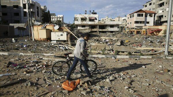 Палестинец идет мимо поврежденного офиса лидера ХАМАСа Исмаила Хании в городе Газа - Sputnik Italia