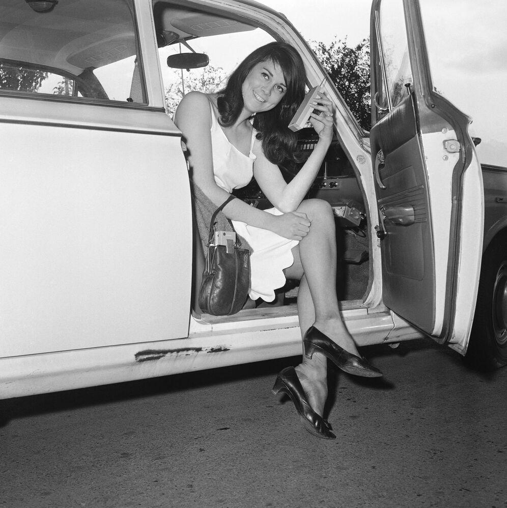 Cambridge, 1965 - Carol Ann Bowler con un telefono in miniatura nella mano sinistra, mentre il ricevitore è nascosto nella sua borsetta