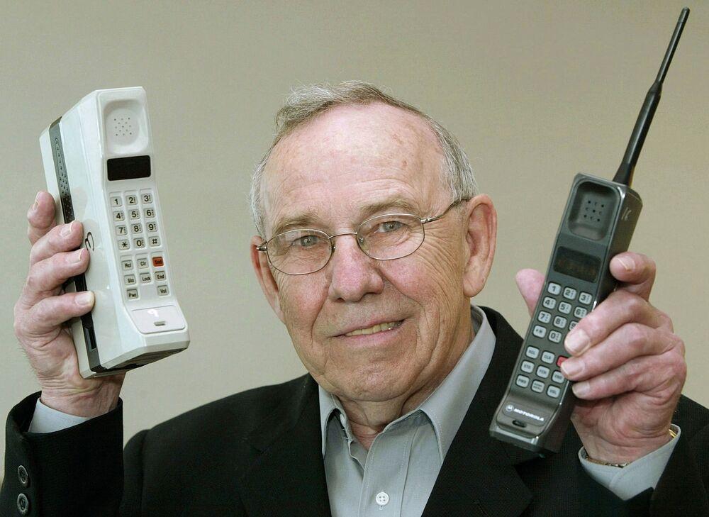 Anno 2003, l'ex capo del reparto Designe della Motorola, Rudy Krolopp, posa con in mano i primi due telefoni cellulari prodotti dalla sua azienda: il DynaTAC 8000X e l'International 3200