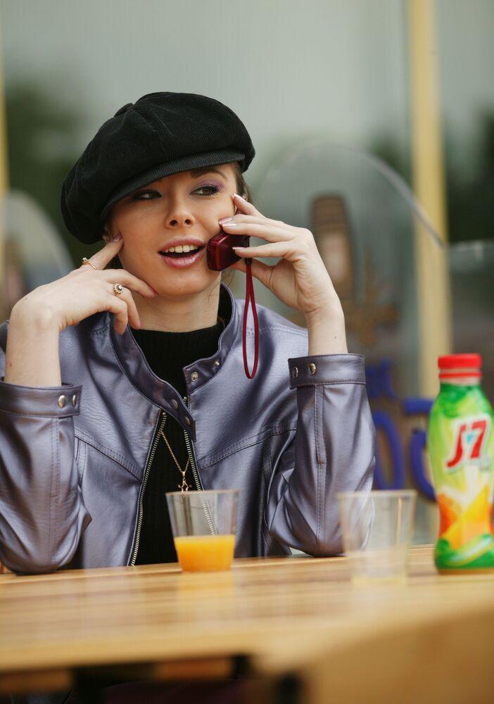 Mosca, 2004 - una ragazza parla al cellulare del suo succo di frutta preferito