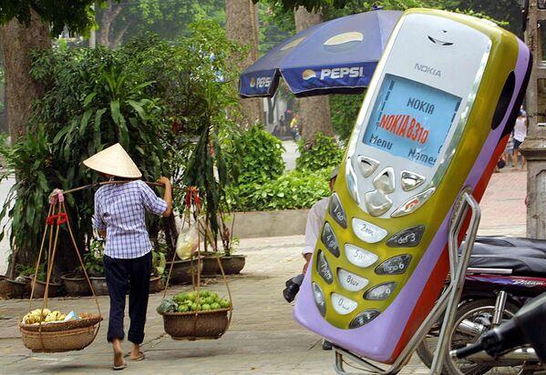 Hanoi, 2002 - Una venditrice di frutta passa accanto ad una riproduzione gigante di un telefonino Nokia 8310 - Sputnik Italia