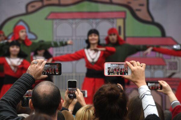 Tbilisi, 2018: spettatori filmano con i propri telefonini l'esibizione di un gruppo folcloristico in occasione del festival culturale Tbilisoba - Sputnik Italia
