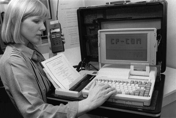 Hannover, CeBit, 1990 - Una ragazza tasta il modellino di un ufficio portatile, contenente un notebook, una stampante ed un telefono portatile.  - Sputnik Italia