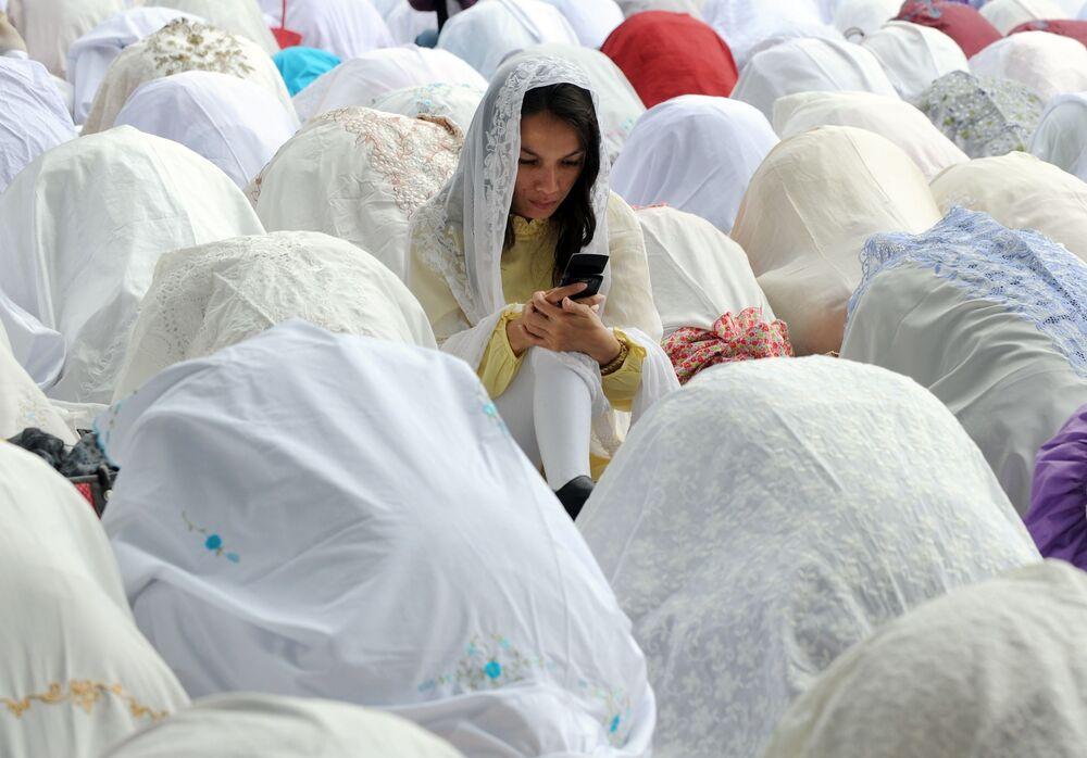 Jakarta, Novembre 2011 - una ragazza musulmana impegnata con il suo smartphone durante il rito dell' Id al-adha, la festa del Sacrificio