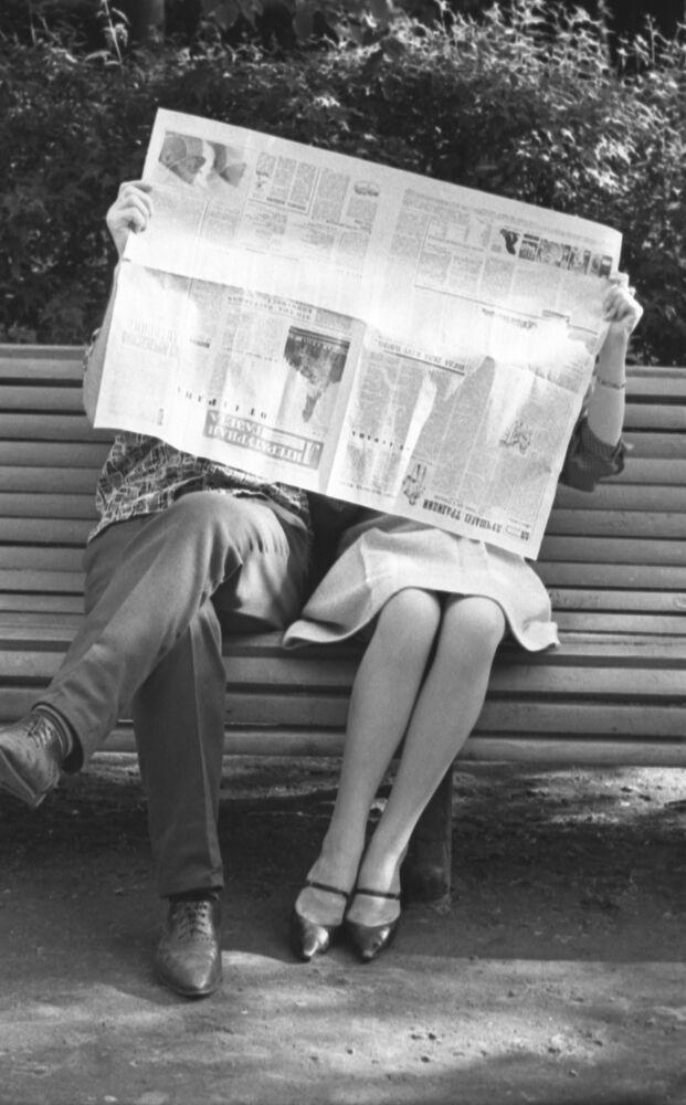 1964 - Dietro la prima pagina del giornale Literaturnaya Gazeta due innamorati si scambiano tenerezze, seduti una panchina di un parco a Mosca. (E non si accorgono che stanno tenendo il giornale al contrario)