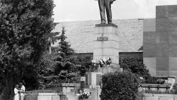 Una coppia di innamorati sotto la statua di Lenin - Sputnik Italia