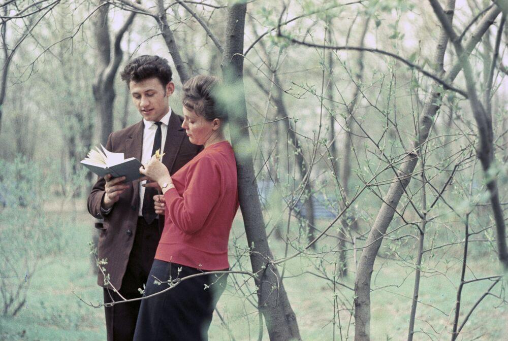 1963 - Versi: una coppia legge insieme un libro di poesie in un parco