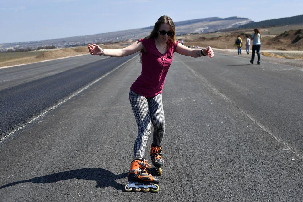 Una ragazza durante il corso sui pattini a rotelle nell'autostrada Tavrida in Crimea.