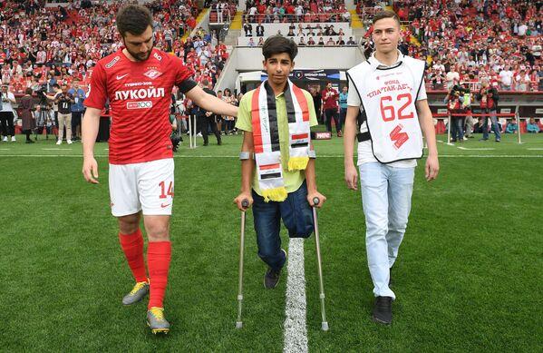 Il capitano dello Spartak Mosca Georgiy Dzhikia accompagna Qasim al centro del campo dello stadio Otkrytie Arena di Mosca, dove il ragazzino iracheno darà il calcio d'inizio della partita Spartak-Ufa  - Sputnik Italia