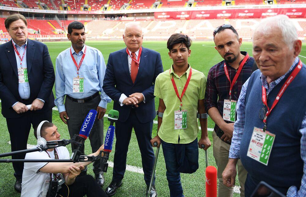 Qasim Alqadim, al centro, insieme al direttore generale di MIA Rossiya Segodnya Dmitriy Kiselev ed al chirurgi Leonid Roshal, che lo visiterà a Mosca per verificare la possibilità di impiantare una protesi alla gamba sinistra