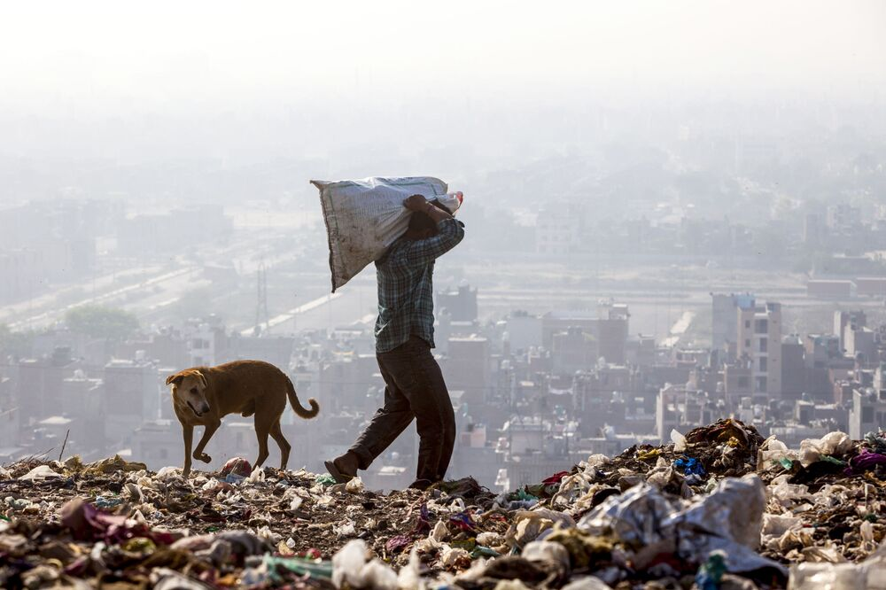 New Delhi, India: un uomo rovista tra i resti dei rifiuti in una discarica