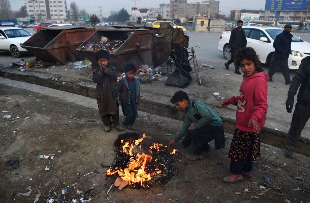 Kabul, bambini afghani danno fuoco a delle gomme per riscaldarsi