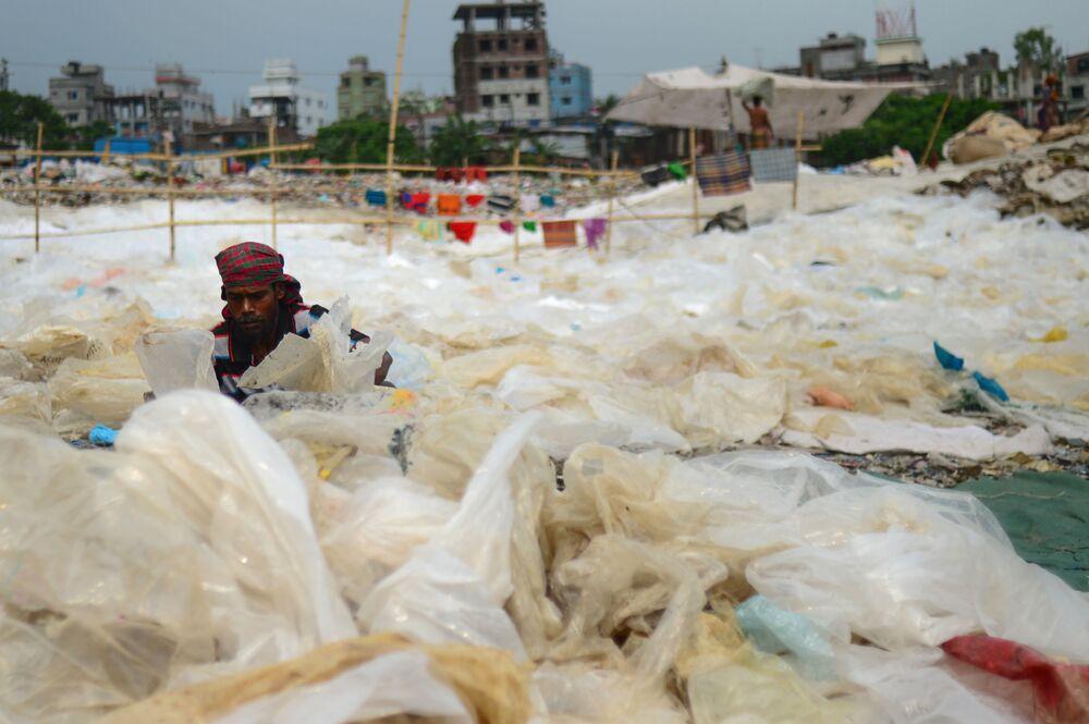 Un uomo circondato dalla plastica in uno dei canali del fiume Buriganga, a Dacca, in Bangladesh