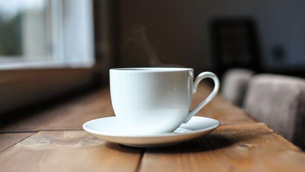 Чашка с горячим напитком на столе - Sputnik Italia
