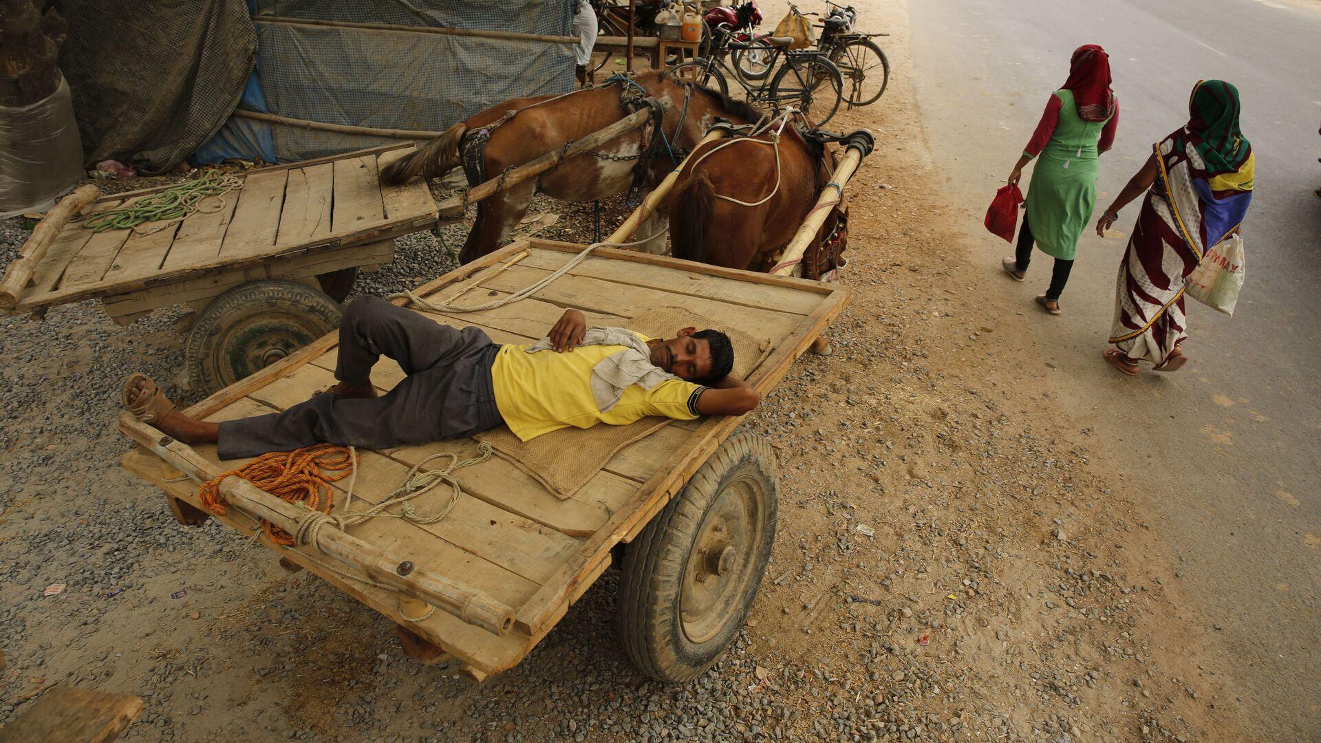 Мужчина спит в повозке во время аномальной жары, Индия - Sputnik Italia, 1920, 30.08.2021