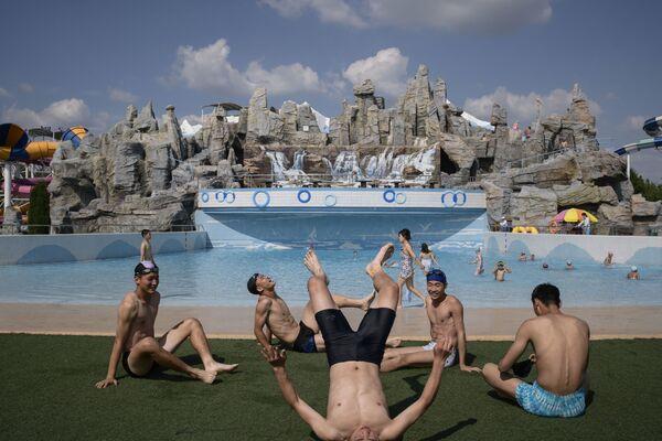 Alcuni ragazzi aggiustano la tintarella tra un bagno e l'altro nell'acquapark Munsu di Pyongyang - Sputnik Italia