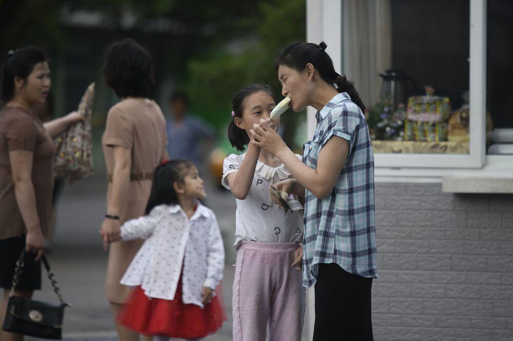 Una donna mangia un gelato con sua figlia in una strada del centro di Pyongyang
