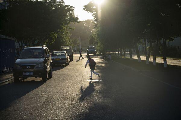 Un bambino gioca tra ombra e sole in una via di Pyongyang - Sputnik Italia