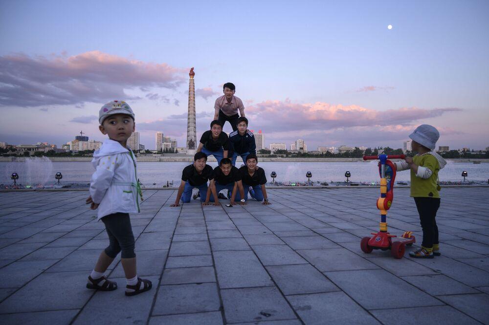 Il caldo dà fastidio anche ai turisti: in questa fotografia un gruppo di giapponesi si dedica ad un pò ginnastica nelle prime ore dell'alba, sul lungofiume Taedong