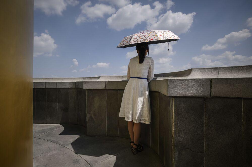 Una ragazza nordcoreana si protegge dal sole con un ombrello