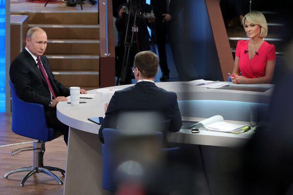 Il presidente russo Vladimir Putin, il corrispondente del VGTRK Pavel Zarubin e il corrispondente del Primo canale Elena Vinnik durante l'annuale programma speciale Linea diretta con Vladimir Putin sui canali televisivi e le stazioni radio russe. - Sputnik Italia