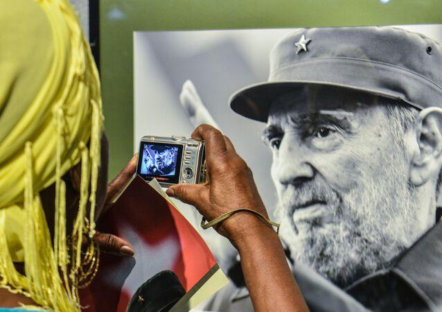 Una donna sta facendo foto al ritratto di Fidel Castro