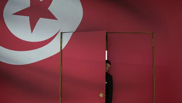 A Tunisian guard looks out of the main gate of media center for its parliamentary election in Tunis, capital of Tunisia, on Oct. 25, 2014 - Sputnik Italia