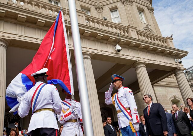A Cuban honor guard prepares the Cuban flag for Cuban Foreign Minister Bruno Rodriguez, center right, before he raises the Cuban flag over their new embassy in Washington, 20, 2015.
