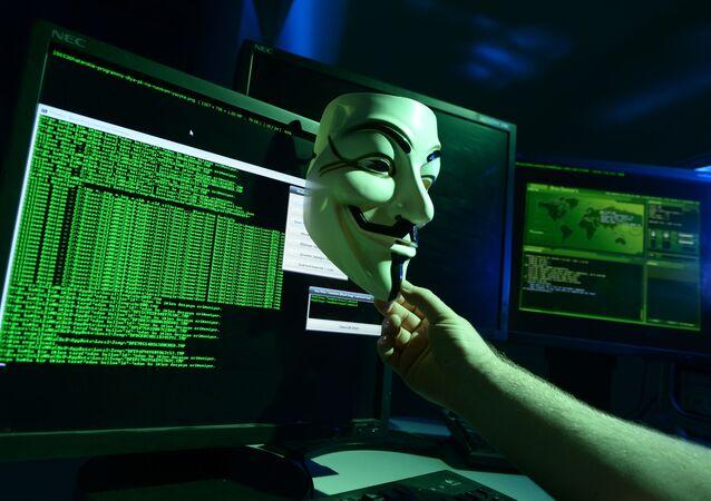 Maschera di fronte a un programma hacher sullo schermo di un computer