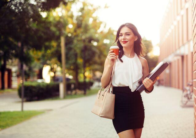 Ragazza cammina con un bicchiere di caffè take-away