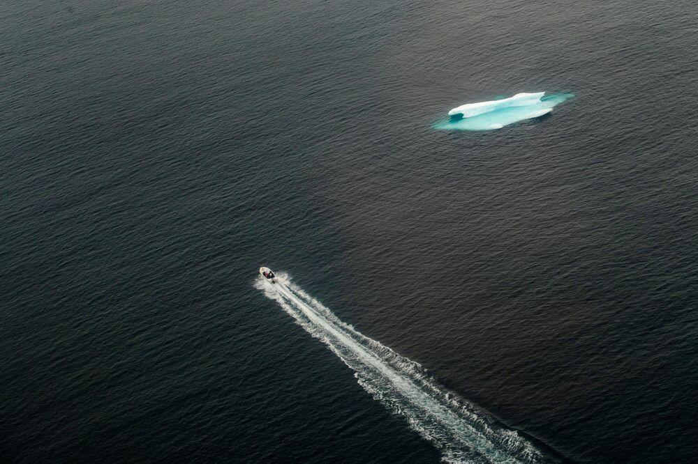Una nave in movimento vicino ad un iceberg in Groenlandia