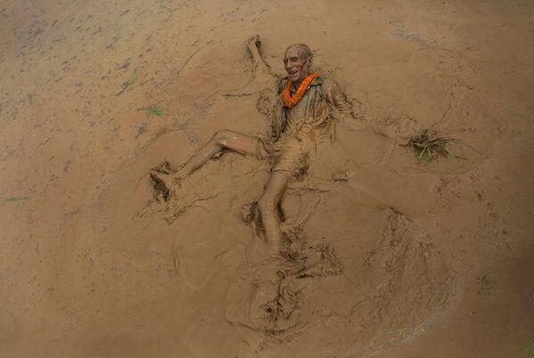 Un uomo anziano si crogiola nel fango nella festa della piantagione del riso ad Asar Pandra in Nepal. - Sputnik Italia
