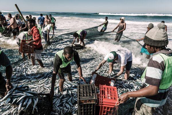 La gente del posto tirsa su le reti da pesca sulla spiaggia di Amanzimtoti, in Sudafrica. - Sputnik Italia