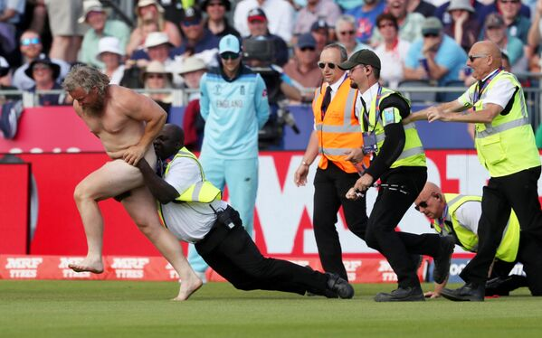 Gli agenti di sicurezza cercano di trattenere un uomo nudo dopo che ha invaso il campo durante una partita di cricket tra Inghilterra e Nuova Zelanda. - Sputnik Italia