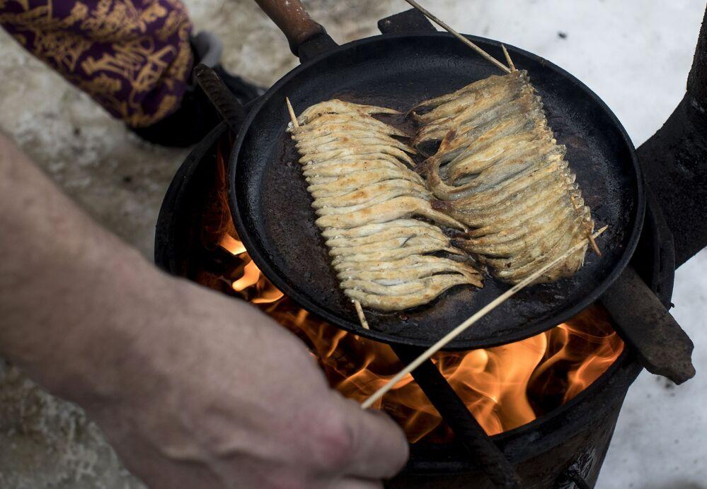 Un pescatore cucina degli sperlani appena pescati in un lago della Lituania